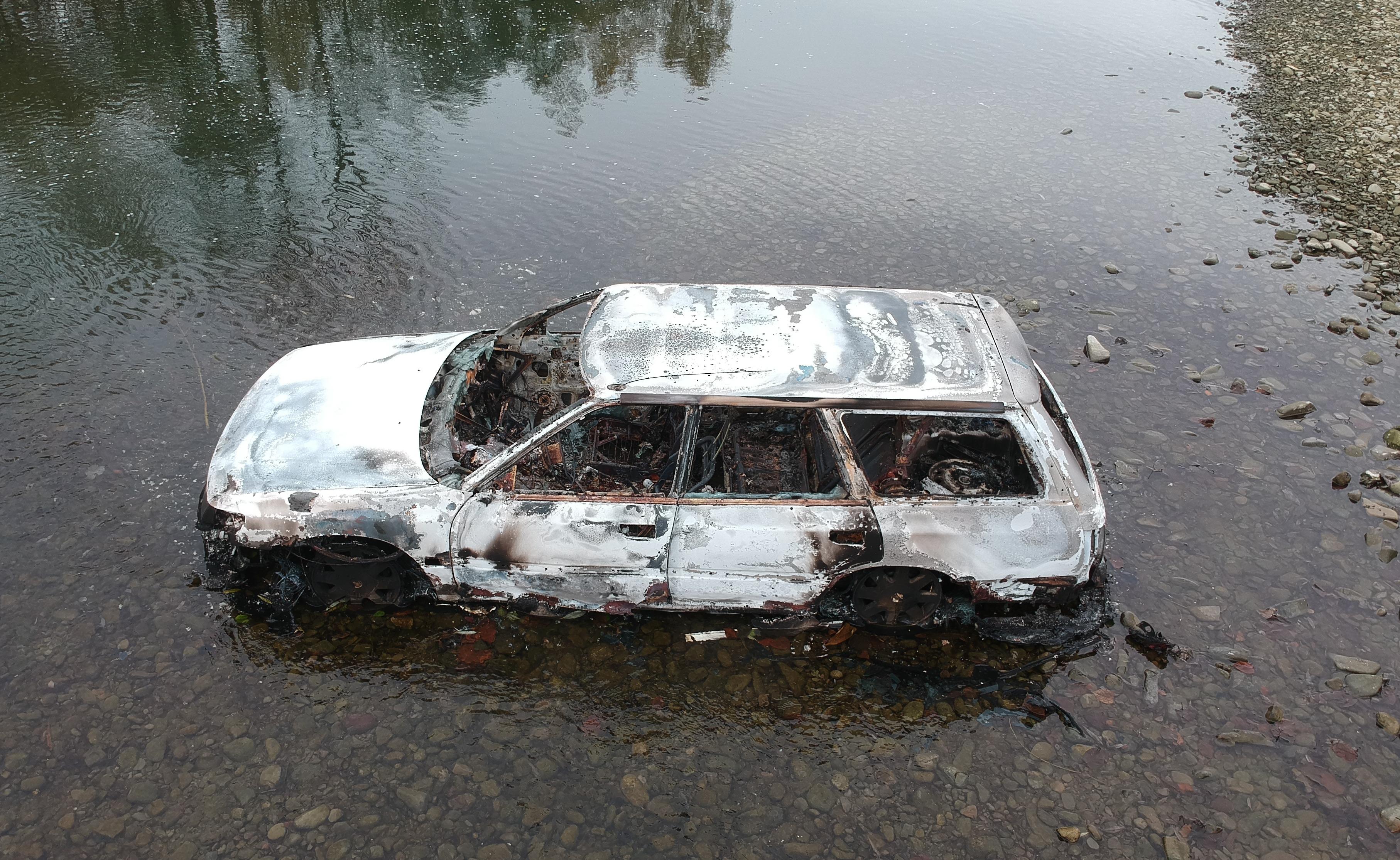 Spalone auto w rzece – ujęcia z drona